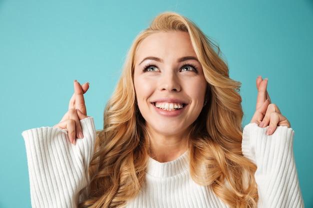 Portrait d'une jeune femme blonde souriante en pull