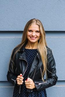 Portrait d'une jeune femme blonde souriante en veste noire debout contre le mur