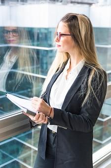 Portrait, de, jeune femme blonde, tenant document, debout, près, les, verre fenêtre