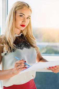 Portrait de jeune femme blonde tenant un document
