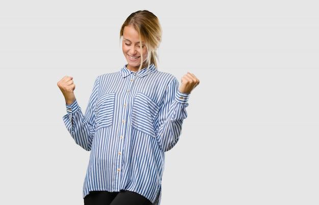 Portrait d'une jeune femme blonde très heureuse et excitée, levant les bras, célébrant une victoire ou un succès