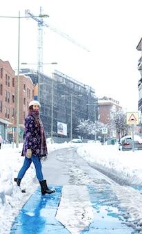 Portrait d'une jeune femme blonde vêtue de vêtements d'hiver marchant dans un passage piéton sur une avenue enneigée de la ville.