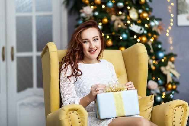 Portrait de jeune femme avec des boîtes de cadeau de noël devant l'arbre de noël