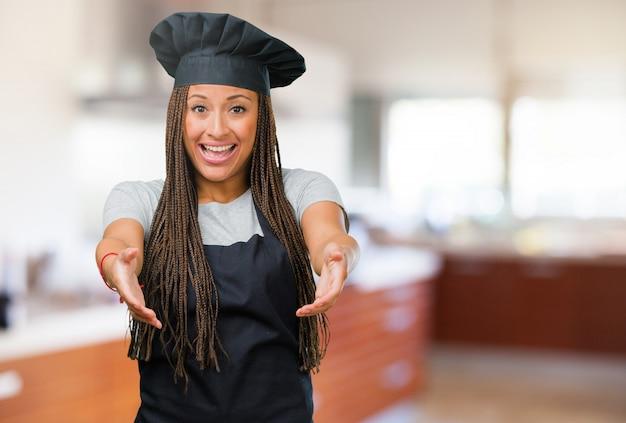 Portrait d'une jeune femme de boulanger noire tendre la main pour saluer quelqu'un ou faire des gestes pour aider, heureuse et excitée