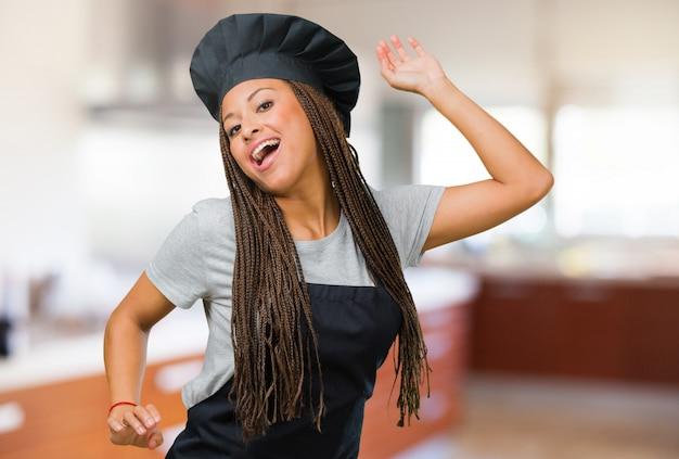 Portrait d'une jeune femme boulangère noire écouter de la musique, danser et s'amuser