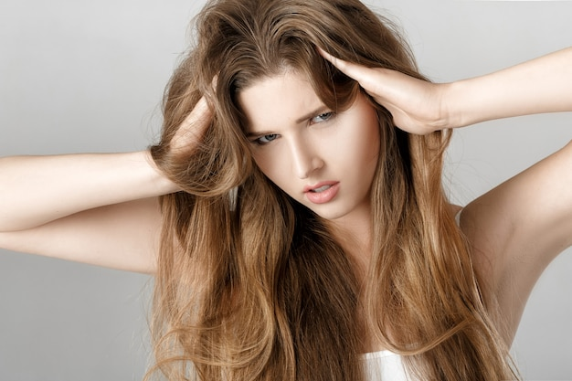 Portrait de jeune femme bouleversée aux cheveux longs.