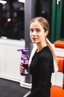 Portrait d'une jeune femme avec une bouteille d'eau