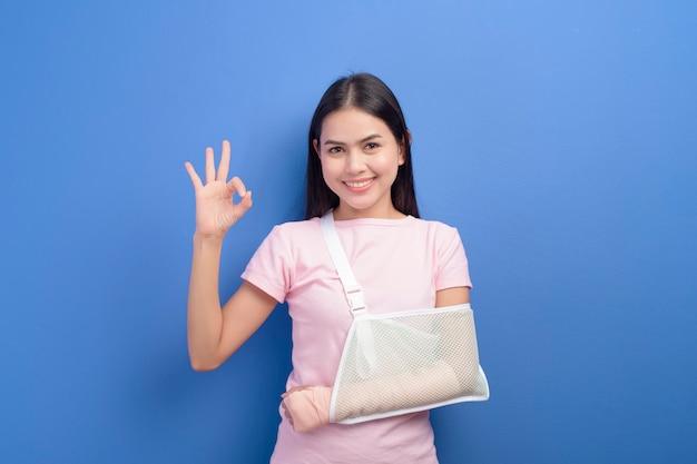 Un portrait de jeune femme avec un bras blessé dans une écharpe sur un mur bleu