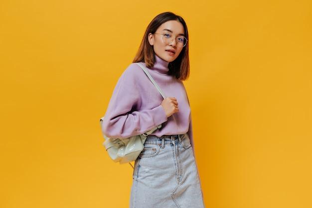 Portrait de jeune femme bronzée aux cheveux courts en lunettes, jupe en jean et pull violet regarde à l'avant et tient un sac à dos à la menthe sur un mur orange