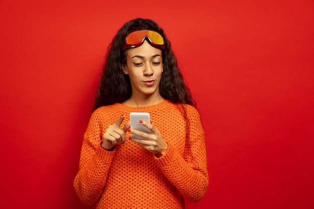 Portrait de jeune femme brune afro-américaine en masque de ski sur l'espace rouge