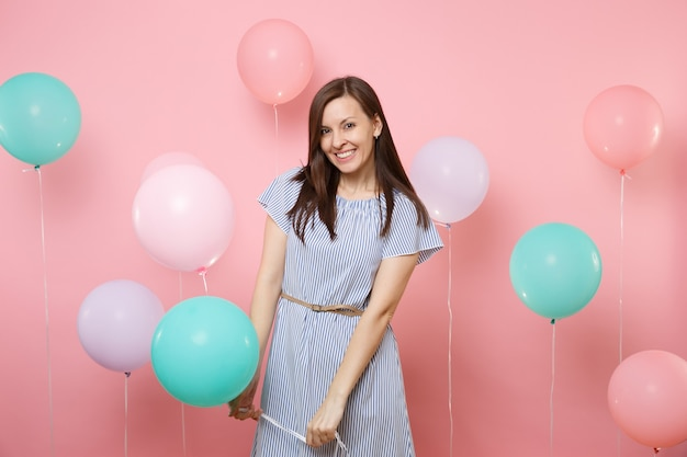 Portrait d'une jeune femme brune assez joyeuse et heureuse vêtue d'une robe bleue tenant des ballons à air colorés sur fond rose tendance lumineux. fête d'anniversaire, concept d'émotions sincères.
