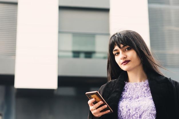 Portrait d'une jeune femme brune aux cheveux longs et aux yeux verts à l'aide de son téléphone portable. lèvres peintes en grenat