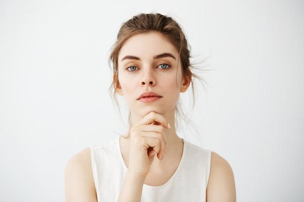 Portrait de jeune femme brune belle posant visage touchant sur fond blanc.