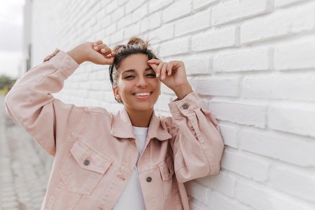 Portrait de jeune femme brune bronzée en veste en jean léger posant contre le bâtiment blanc