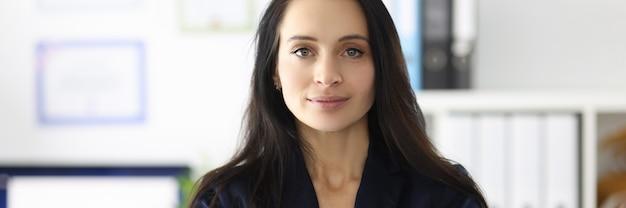 Portrait de jeune femme brune en costume d'affaires dans la mise en œuvre de bureau de femmes d'affaires
