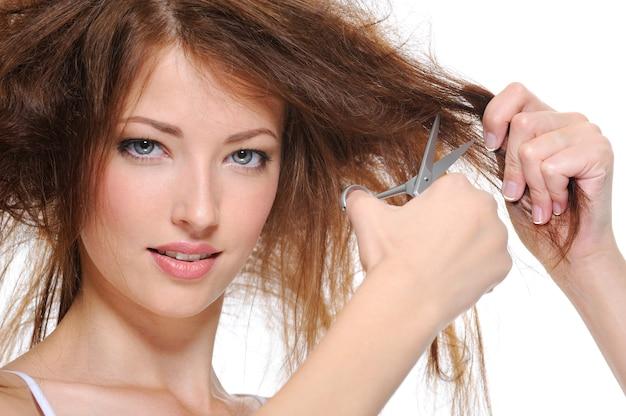 Portrait de jeune femme brune coupant ses cheveux isolé sur blanc