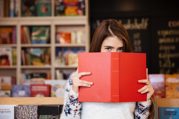 Portrait d'une jeune femme brune couvrant son visage avec un livre avec une bibliothèque en arrière-plan