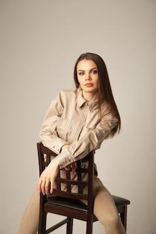 Portrait de jeune femme brune dans un chemisier beige posant sur la chaise et regardant l'avant sur une surface beige