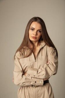 Portrait de jeune femme brune dans un chemisier beige posant et regardant l'avant sur une surface beige
