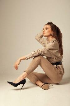Portrait de jeune femme brune dans un chemisier beige posant sur le sol et regardant à l'avant sur une surface beige