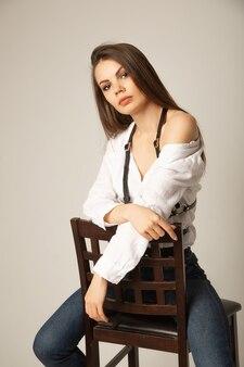 Portrait de jeune femme brune dans un chemisier blanc, un jean et un harnais posant sur la chaise et regardant l'avant sur une surface beige