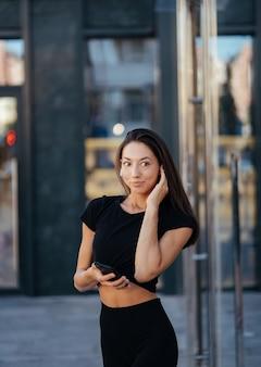 Portrait d'une jeune femme brune avec des écouteurs et souriant en marchant
