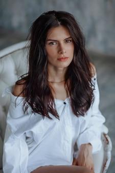 Portrait de jeune femme brune sur fond clair