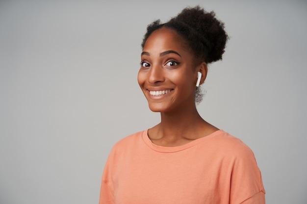 Portrait de jeune femme brune frisée joyeuse à la peau foncée avec un sourire charmant tout en écoutant de la musique dans ses écouteurs, posant sur fond gris