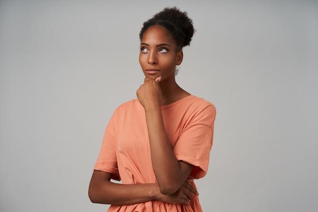 Portrait de jeune femme brune frisée à la peau assez sombre tenant son menton avec la main levée et roulant ses yeux bruns tout en posant sur le gris