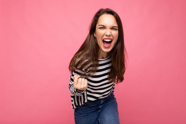 Portrait d'une jeune femme brune heureuse et heureuse avec des émotions sincères portant un pull rayé décontracté isolé sur fond rose avec un espace vide et célébrant la victoire en criant oui.