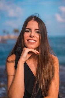 Portrait d'une jeune femme brune heureuse avec la mer à torrevieja, alicante, espagne