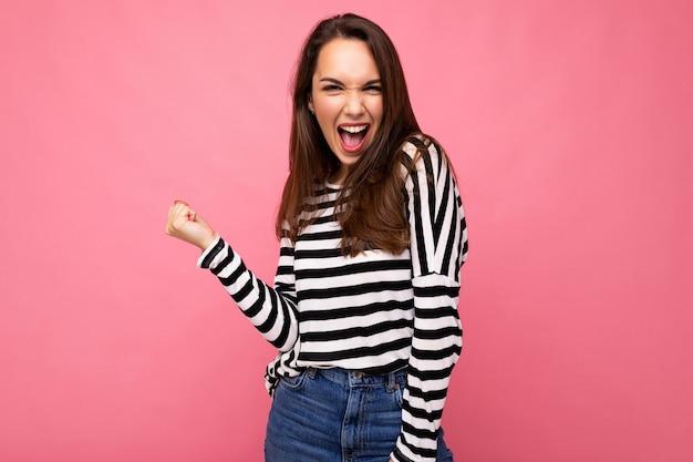 Portrait d'une jeune femme brune heureuse et positive émotionnelle avec des émotions sincères portant un pull rayé isolé sur fond rose avec un espace vide et célébrant la victoire en criant oui.