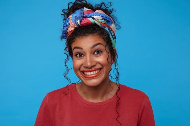Portrait de jeune femme brune joyeuse avec des cheveux bouclés rassemblés à la caméra avec un large sourire, debout sur fond bleu dans des vêtements colorés