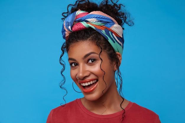 Portrait de jeune femme brune mignonne bouclée avec maquillage festif étant de bonne humeur et souriant joyeusement en se tenant debout sur un mur bleu dans des vêtements colorés
