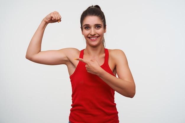Portrait de jeune femme brune mignonne souriante porte en t-shirt rouge montre un beceps et pointe son doigt sur ses muscles. se dresse sur fond blanc et sourit largement.