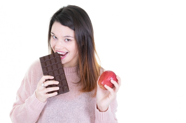 Portrait d'une jeune femme brune mordant au chocolat avec une pomme rouge à la main