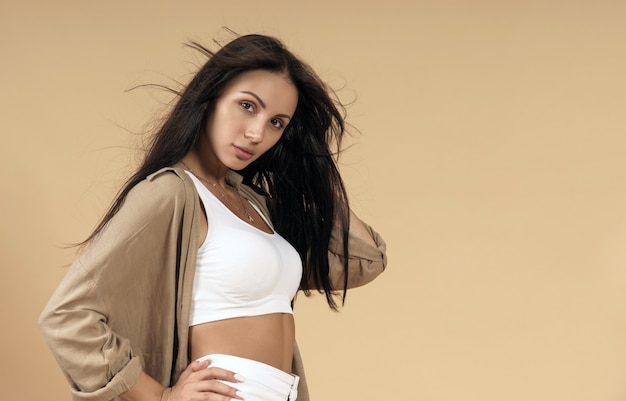Portrait de jeune femme brune sur mur beige