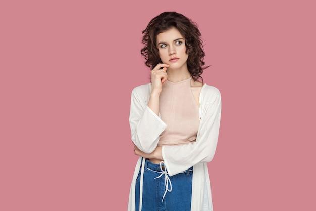 Portrait d'une jeune femme brune réfléchie avec une coiffure frisée dans un style décontracté debout, touchant son menton, détournant les yeux et pensant quoi faire. tourné en studio intérieur isolé sur fond rose.