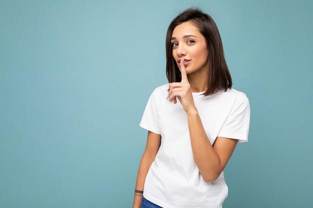 Portrait de jeune femme brune séduisante avec des émotions sincères portant un t-shirt blanc décontracté pour maquette isolé sur fond bleu avec espace copie et demandant de rester silencieux.