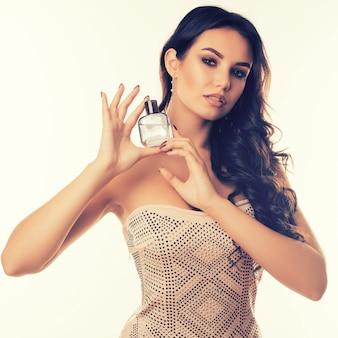 Portrait d'une jeune femme brune sensuelle avec une bouteille de parfum de luxe dans ses mains isolé sur blanc.