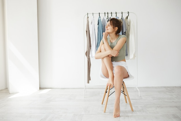 Portrait de jeune femme brune souriante regardant à côté assis sur une chaise sur une penderie et un mur blanc.