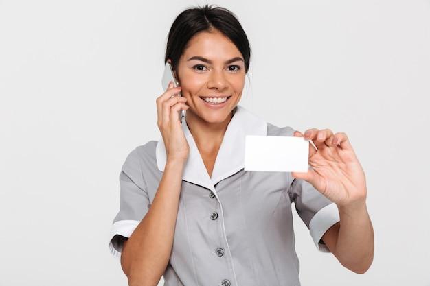 Portrait de jeune femme brune souriante en uniforme parler sur téléphone mobile tout en montrant la carte de signe vide