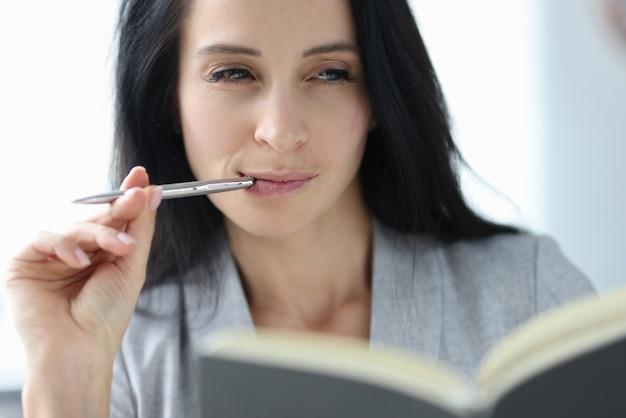 Portrait de jeune femme brune avec un stylo à bille dans sa bouche. concept de journalisme