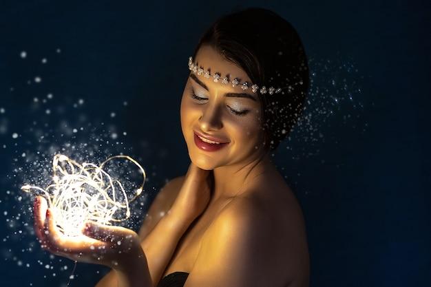 Portrait d'une jeune femme brune tenant une boule rougeoyante de lumières led.