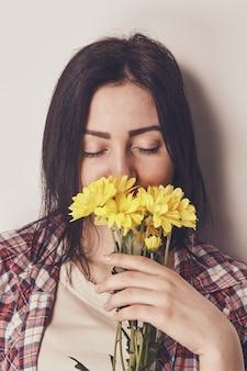 Portrait d'une jeune femme brune vêtue d'une chemise à carreaux sentant un bouquet de fleurs jaunes