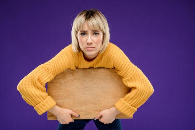 Portrait de jeune femme avec bureau en bois sur mur violet