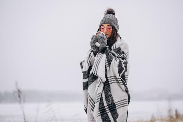 Portrait de jeune femme buvant du café dans un parc d'hiver