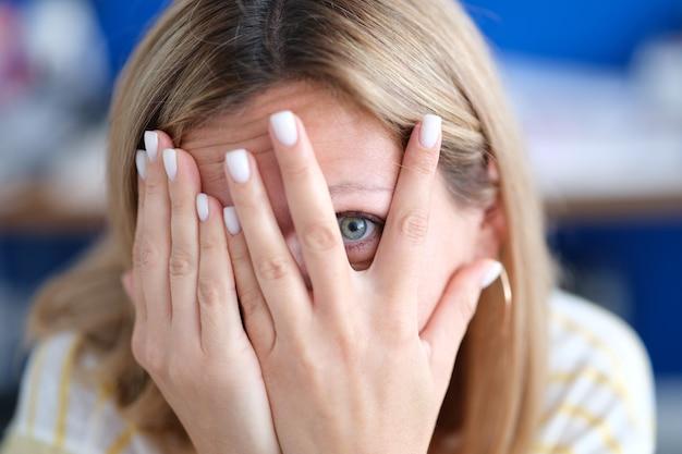 Portrait de jeune femme cache le visage et regarde à travers les doigts doute de soi et faible estime de soi