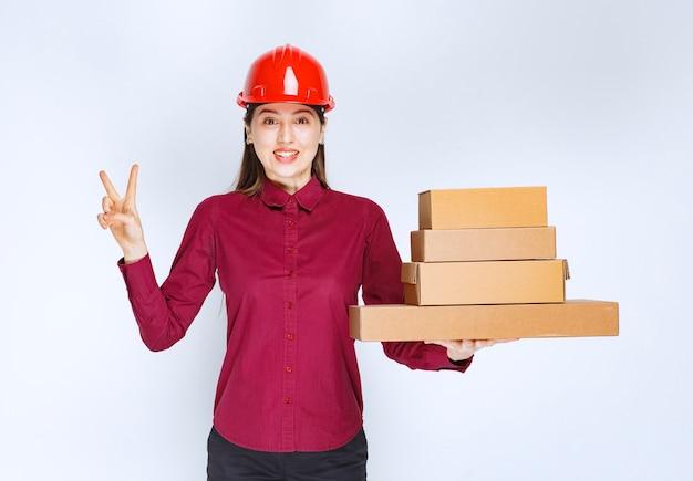 Portrait d'une jeune femme en casque de protection avec des boîtes en papier montrant le signe de la victoire.