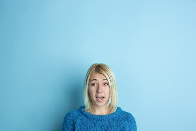 Portrait de jeune femme caucasienne a l'air rêveur, mignon et heureux. penser, se demander, rêver sur l'espace bleu